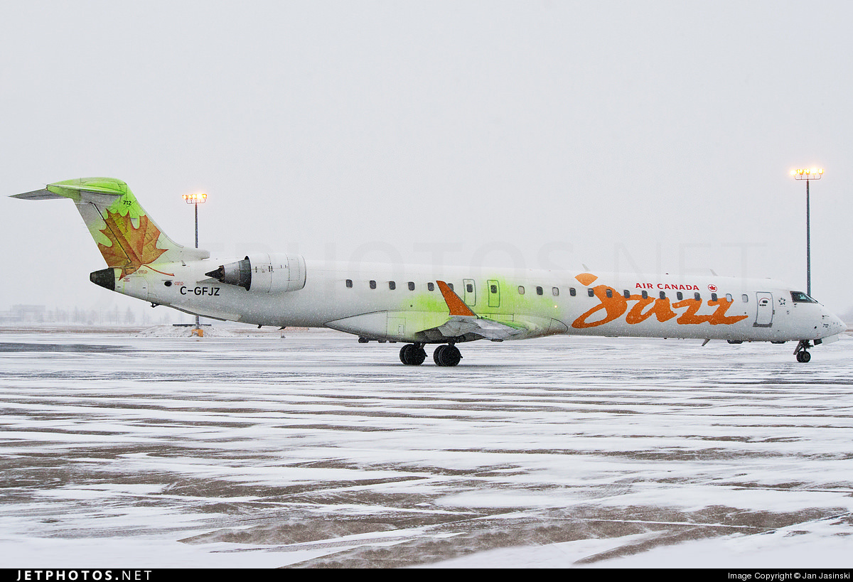 An Air Canada Jazz CRJ-700 taxiing covered in Type IV deicing fluid.