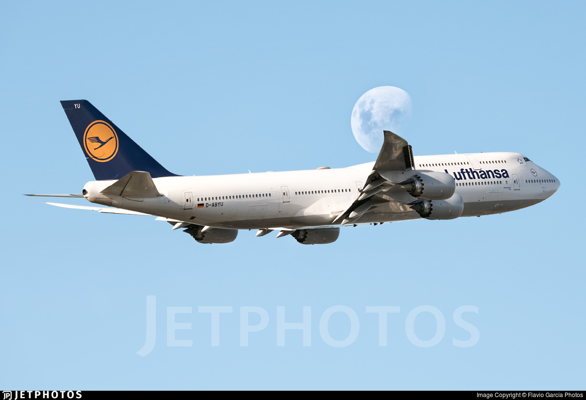 A daytime moon creates a halo around the right wing of a Lufthansa 747-8I departing Buenos Aires
