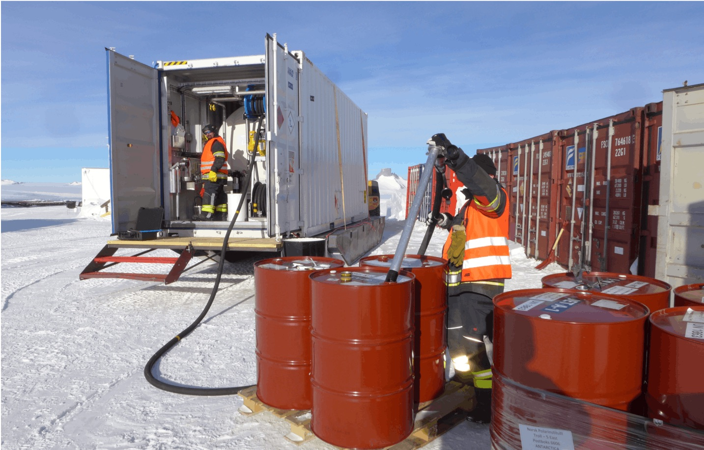 Staff transfer fuel from 200 liter drums to a 16,000 liter tank pressure fueler